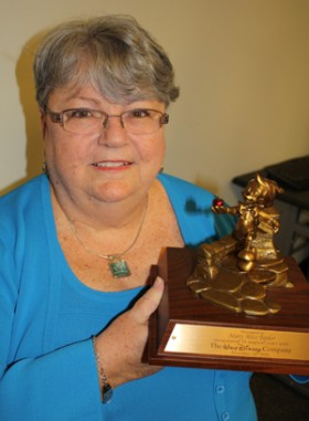 Walt Disney's costume buyer, Mary Alice Taylor '78, holding the award she got for 35 years of loyal service.