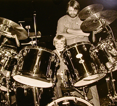 A very young Christopher Swist, under the watchful eye of his father, trying his hand on the stage drum set during a 1979 Chuck Mangione tour.