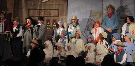 "Lorrie Gray (far left) and Rob Gray '88 (in blue shirt, red bandanna, and cowboy hat) with the troupe in ""Emperor's New Clothes"""
