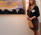Courtney Lachaussie '14 with one of her landscapes at the Bryan Memorial Gallery