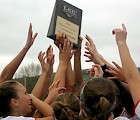 KSC Women's lacrosse team hoists their LEC championship trophy.