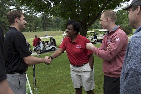New Athletic Director Kristene Kelly (center) greets Tyler Hundley, assistant men's basketball coach, and Ryan Cain, head men's basketball coach, at the annual golf tournament. Photo by Will Wrobel
