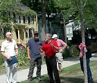 Bud Winsor (center, in red shirt) at the dedication of the Kentucky coffee tree (with red and white ribbon) to honor retiring Keene State arborist Jeff Garland (left, in creme shirt)