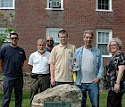 "At the monument to Nathan Blake, on the Main Street side of Blake House (l–r): grounds staff Noah Washburn, Bud Winsor, and Joe Britton; Tuck Abert; Ernie Hebert '69 (with a copy of ""The Old American""); and Nancy Howard, regent of the Ashuelot DAR"