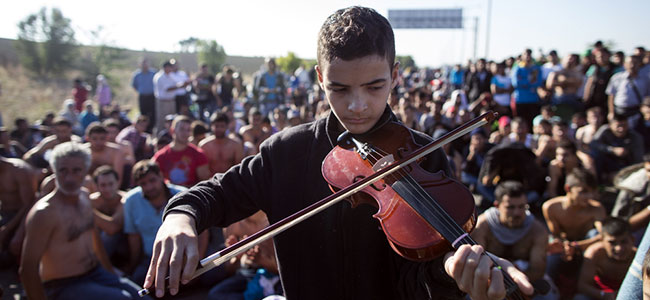 Syrian boy plays the violin at refugee encampment, Edirne, Turkey, September 2015
