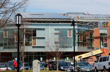 An array of solar panels is being installed on top of the new TDS building