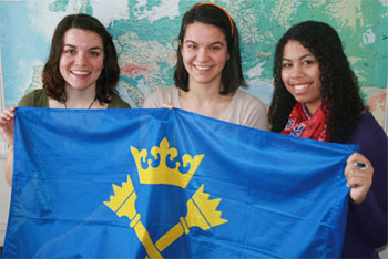 Holocaust and Genocide Studies students Johanna DeBari (left) and Chloe Edmonds (right) hold the Jagiellonian University flag with Justyna Jochym (middle) who coordinates the Jagiellonian study-away program.