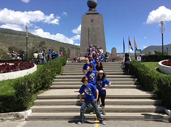 Students line up at 0 degrees to take photos at Mitad del Mundo