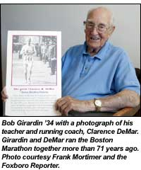 Bob Girardin '34 with a photograph of his teacher and running coach, Clarence DeMar. Girardin and DeMar ran the Boston Marathon together more than 71 years ago. Photo courtesy Frank Mortimer and the Foxboro Reporter.