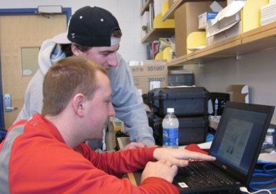 Students Jeff Pelkey (sitting) and Joe Frechette (standing) working on data analysis in the lab