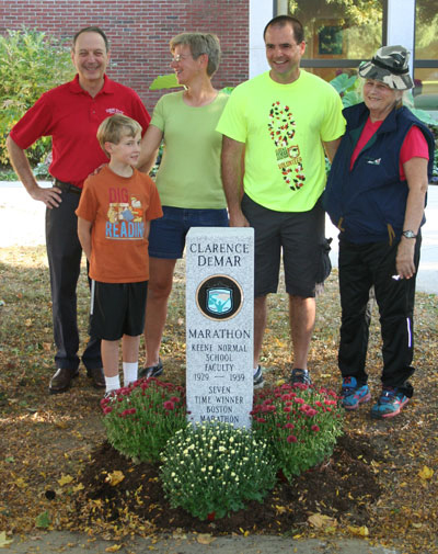 Jay Kahn, Keene State VP for Finance and Planning (at left), is joined by Clarence DeMar's granddaughter and great-grandson, race director Alan Stroshine, and Clarence DeMar's daughter, Betty DeMar-Mueller at the DeMar marathon finish line marker on Appian Way.