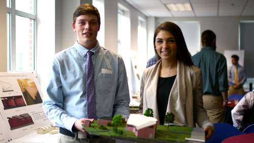 Logan Mott and Kayla Gallo display their model for an addition to the Tunga Primary School in Malawi.