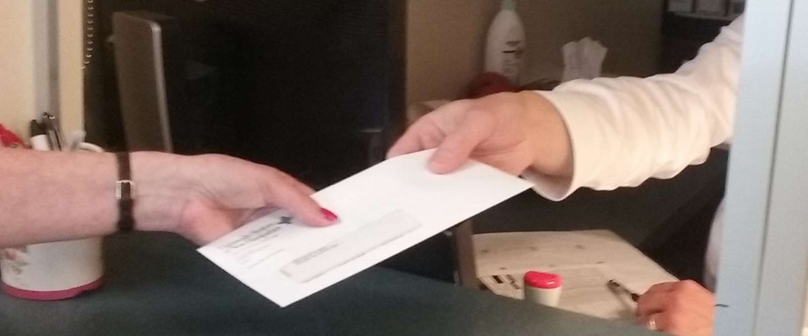 Envelope/Check Being Handed Over