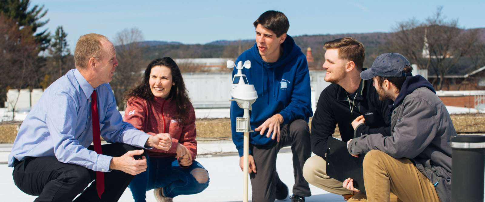 Professor Chris Cusack, left, and his students gather around a weather station on the roof of the Science Center.