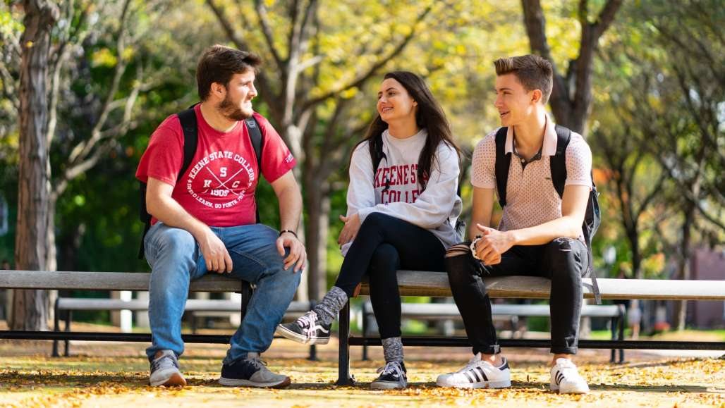 Students on Bench in the Fall