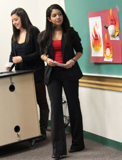 Team members Stacie Coleman (left) and Gabrielle Gentilella present their plan to promote awareness of campus tobacco policy.
